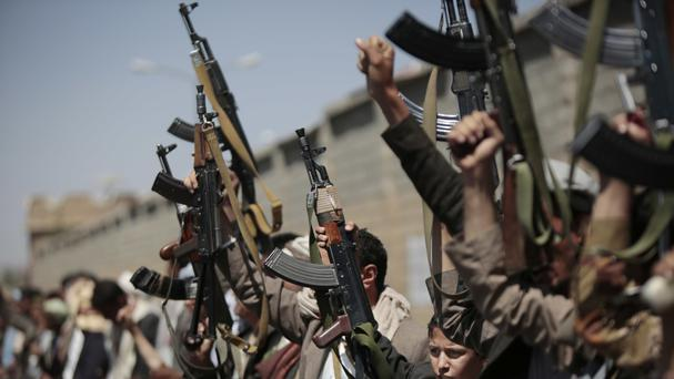 Tribesmen loyal to Houthi rebels hold their weapons high as they chant slogans during a gathering (AP)