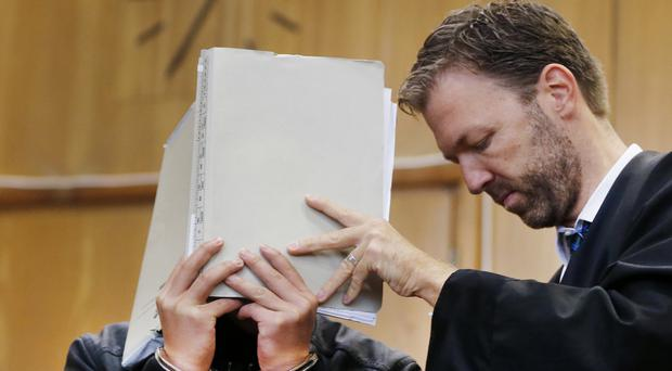 A 16-year-old covers his face in a court after being accused of murder following the death a 41-year-old woman in an apparent exorcism ritual (AP)