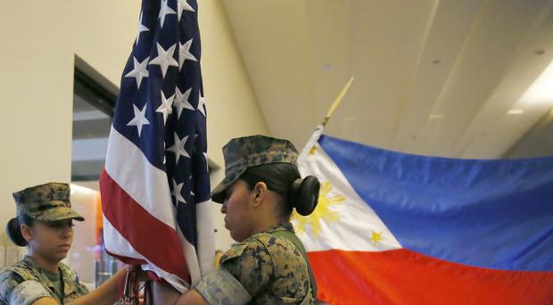 US Marines and their Philippine counterparts fold their respective flags at the closing ceremony of the 33rd joint US-Philippines amphibious landing exercises (AP)
