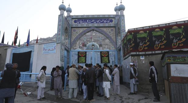 Afghans stand in front of the shrine after a militant attack in Kabul, Afghanistan. (AP)