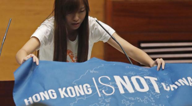 Newly-elected lawmaker, Yau Wai-ching displays a banner with words reading Hong Kong is not China as she takes oath in the new legislature Council in Hong Kong. (AP)