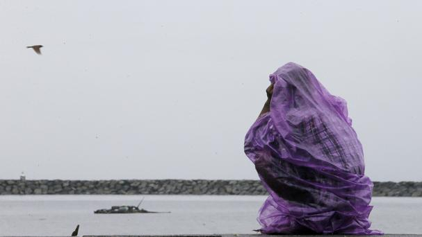 A fisherman sits on a promenade under rain brought about by Typhoon Karika (AP)