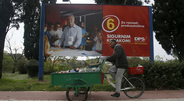 A man passes an election poster for pro-Western prime minister Milo Djukanovic (AP)