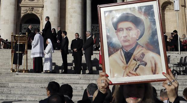 A woman holds a portrait of Argentine