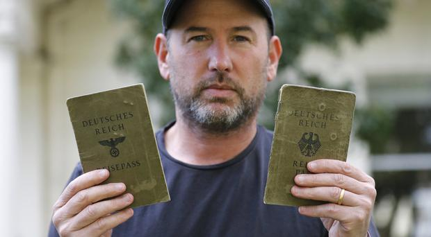 Thomas Harding shows the passports of his grandparents (AP)
