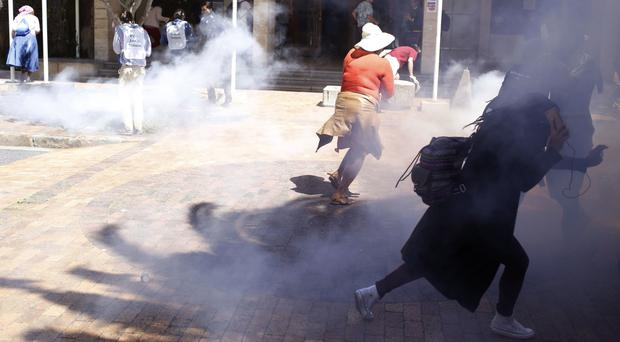 Students run away from a stun grenade used by police at the University of Cape town campus (AP)