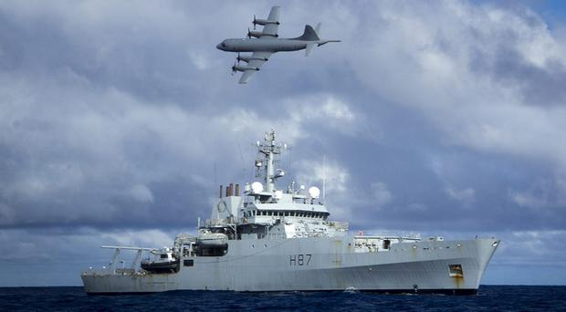 A Lockheed P-3 Orion flies over survey ship HMS Echo in the southern Indian Ocean during the search for the flight recorder from missing Malaysia Airlines flight 370 (MoD/PA)