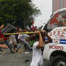 Protesters hit a Philippine National Police van after it rammed into protesters outside the US embassy in Manila (AP)
