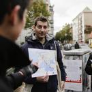Syrian refugee Firas Zakri shows a map as he gives a tour of the district of Neukoelln in Berlin (AP)
