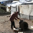 A Syrian woman cooks outside her tent at Ritsona refugee camp north of Athens (AP)