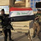 Iraq's elite counterterrorism force soldiers raise an Iraqi flag in front of a church