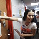 Katy Perry covers the peephole of a dorm room door after knocking on it while canvassing for Hillary Clinton (AP)
