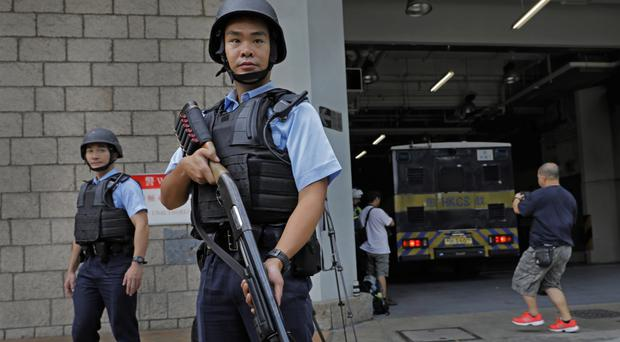 Police guard the prison bus carrying British banker Rurik Jutting at the High Court in Hong Kong (AP)