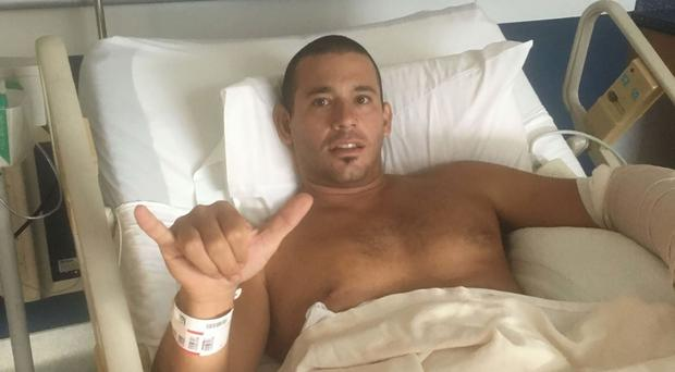Surfer Federico Jaime poses for a photo in his hospital bed in Wailuku, Hawaii, after the shark attack (Kari Feinstein/AP)