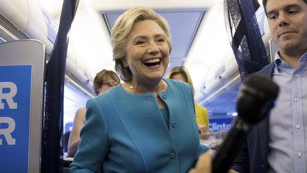 Democratic presidential candidate Hillary Clinton brings birthday cake back to members of the media aboard her campaign plane (AP)