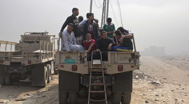 Displaced persons sit inside an army truck at a checkpoint in Qayara, south of Mosul (AP)