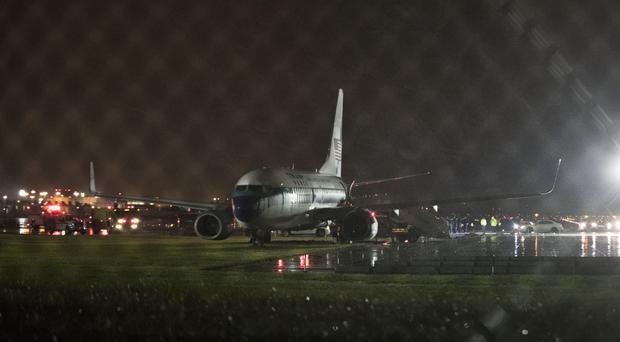 Mike Pence's campaign plane sits partially on the tarmac and the grass after sliding off the runway (AP)