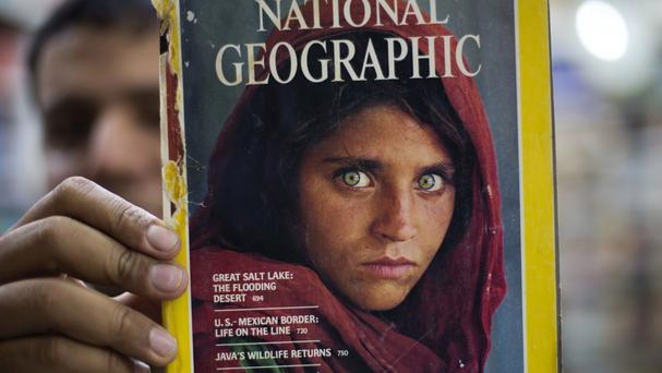 Bookshop owner Inam Khan shows a copy of a magazine featuring the photograph of Afghan refugee woman Sharbat Gulla (AP)