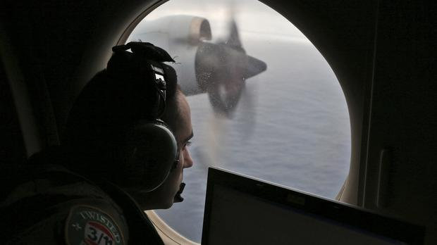 Flight officer Rayan Gharazeddine scans the water in the southern Indian Ocean from a Royal Australian Air Force AP-3C Orion during the search for Malaysia Airlines Flight MH370 (AP)