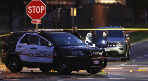 Police gather evidence at the scene of one of the shootings (AP)