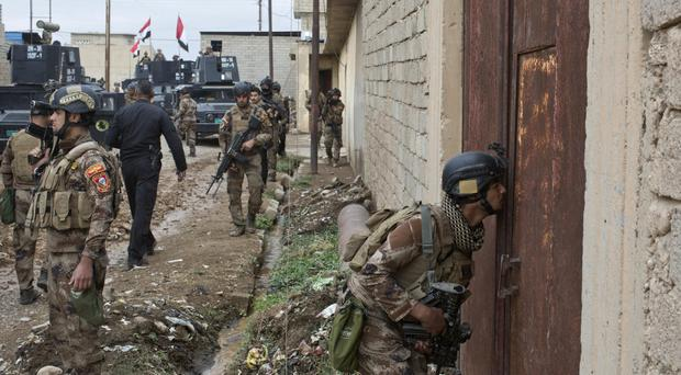 Iraqi special forces prepare to search a compound in Gogjali, an eastern district of Mosul (AP)