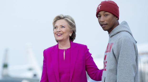 Hillary Clinton and singer-songwriter Pharrell Williams arrive at Raleigh-Durham Airport in North Carolina (AP)