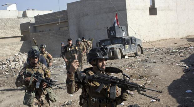 Iraqi special forces soldiers move in formation in Mosul