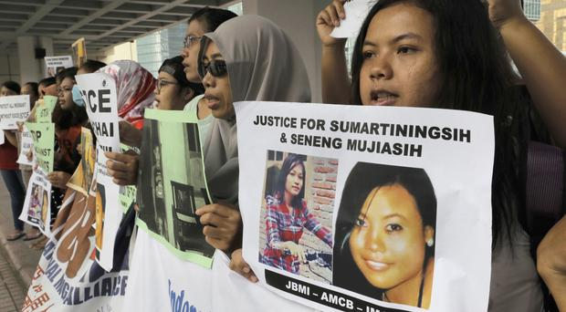 Protesters outside the High Court in Hong Kong, where Briton Rurik Jutting has been found guilty of murdering two Indonesian women (AP)