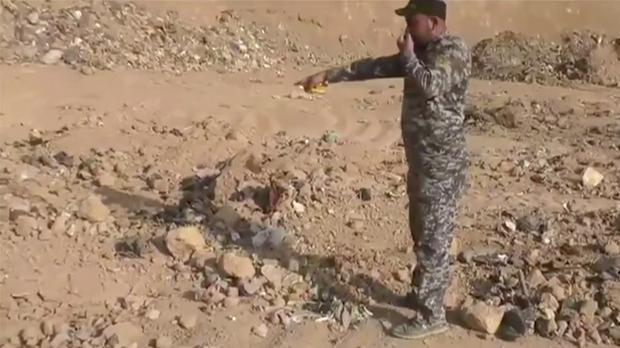 An Iraqi federal police officer points towards a mass grave discovered in Hamam al-Alil, Iraq (AP)