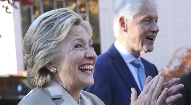 Democratic presidential candidate Hillary Clinton and her husband, former president Bill Clinton, greet supporters after voting in Chappaqua, New York (AP)