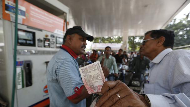 An employee of a fuel pump argues with a customer for change of 1000 rupee Indian currency note in Ahmadabad, India. (AP)