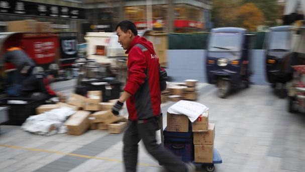 A delivery worker pulls a cart loaded with goods as online shoppers spent billions on Singles Day. (AP)