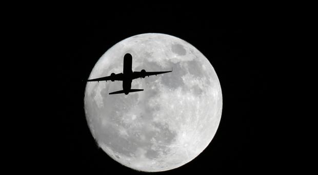 An plane passes in front of the moon, as seen from Whittier, California (AP)
