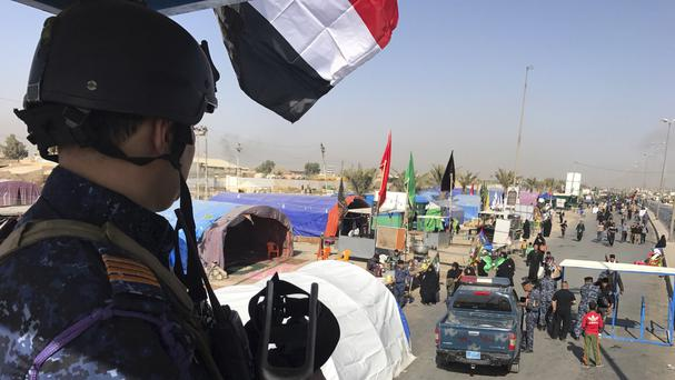 Iraqi federal police guard Shiite pilgrims marching toward Karbala (AP)
