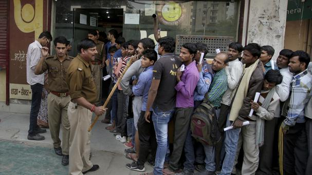 A police officer warns people against breaking the queues as they wait to exchange or deposit discontinued currency notes (AP)