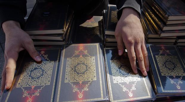 A member of a Muslim group prepares copies of the Koran for distribution at Potsdamer Platz in Berlin (AP)