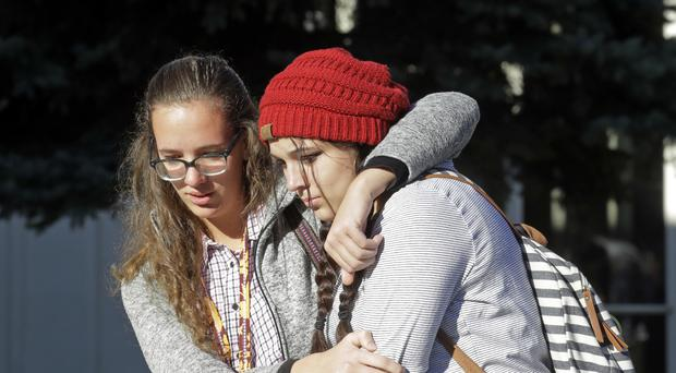Students Albany Cox, right, and Holly Hilton leave Mountain View High School where several students were stabbed (AP)