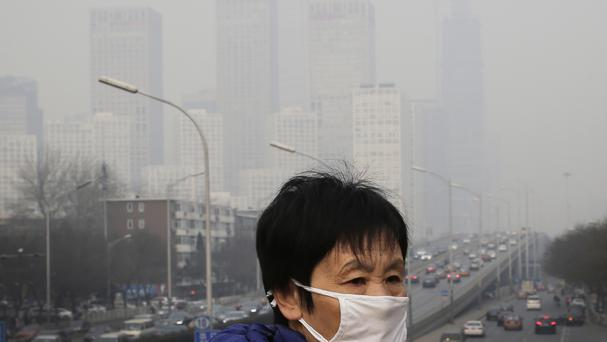 A woman wearing a mask for protection against pollution as office buildings are shrouded with smog in Beijing (AP)
