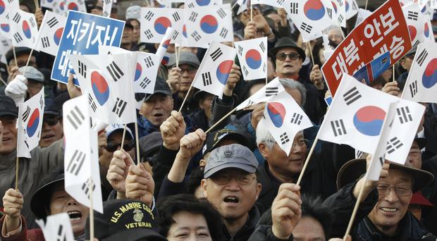Protesters supporting South Korean President Park Geun-hye wave national flags during a rally opposing her resignation in Seoul (AP)