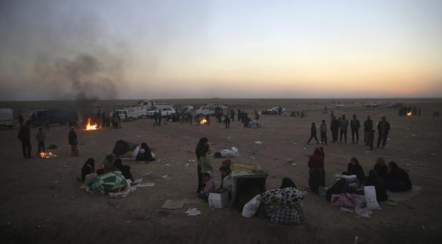 Iraqi families who fled the fighting between Iraqi forces and Islamic State militants wait to cross to the Kurdish controlled area north-east of Mosul (AP)