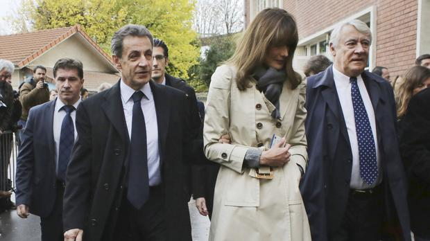 Former French president Nicolas Sarkozy and his wife Carla Bruni-Sarkozy leave the polling station after casting their votes for the conservative primary election (AP)