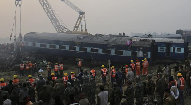 Rescuers work at the site after 14 coaches of an overnight passenger train rolled off the track (AP)