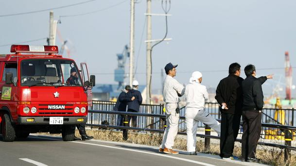 Firefighters watch the port to check the water level as a tsunami warning is issued following an earthquake in Soma, Fukushima prefecture, northern Japan (AP) (Kyodo News/AP)