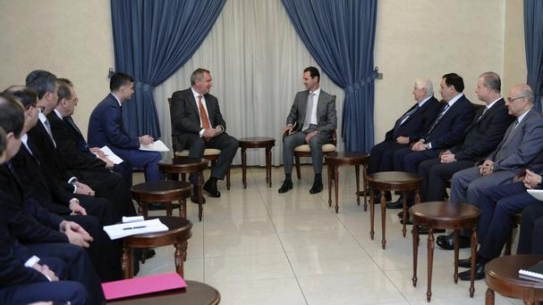 Syrian president Bashar Assad, centre right, meets a Russian delegation in Damascus (SANA/AP)