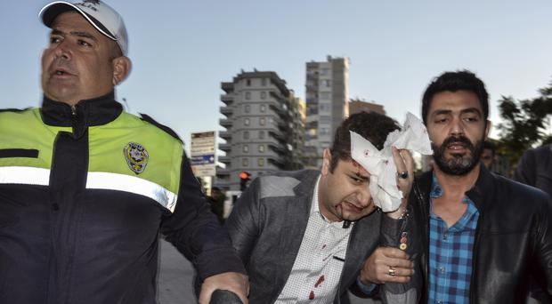 A police officer and a civilian help a wounded person after an explosion that killed people and wounded several others in southern city of Adana, Turkey.