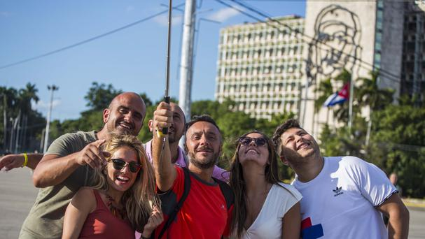 Tourists take selfies with an image of Cuba's revolutionary hero Che Guevara in the background, at Revolution Square in Havana (AP)