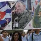 Young Cubans hold pictures of Fidel Castro at the rally at the Revolution Plaza in Havana (AP)