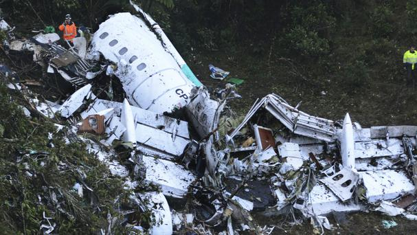 Rescue workers search the wreckage of the charter plane (AP)