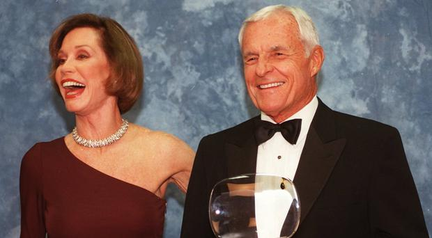 Grant Tinker holds up his Academy of Television Arts & Sciences' Hall of Fame award alongside ex-wife Mary Tyler Moore in 1997 (AP)