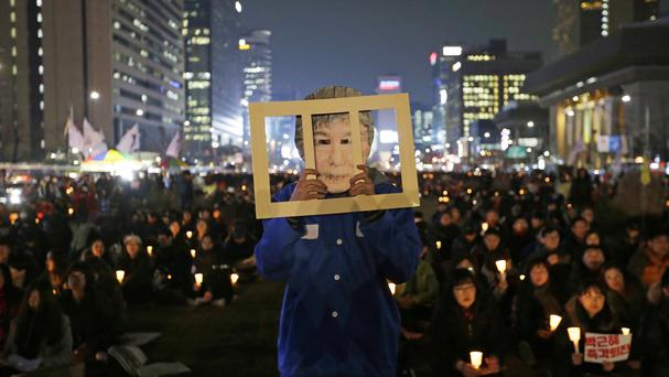 Park Geun-hye faces protests over allegations that she allowed a confidante to pull government strings and extort businesses (AP)